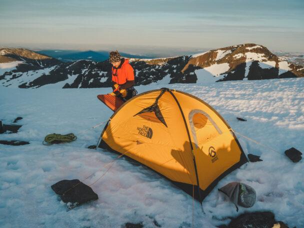 En person invid ett tält på en snöig bergsplätt