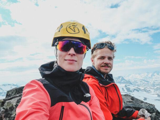Emma och Anton i klättermundering framför ett dimmigt bergslandskap