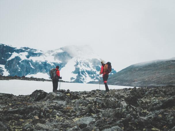 Två personer på en stenig häll framför ett snöigt berg