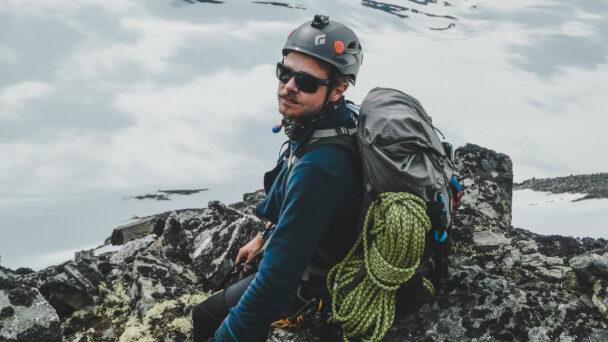 Anton Levein i klätterutrustning på en klippkam framför ett molnigt bergslandskap
