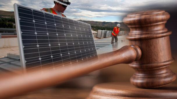 En domarklubba monterad över två personer installerar solceller på ett tak
