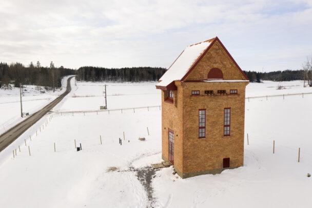 Transformatortornet, en hög tegelbyggnad, på en snöig åker