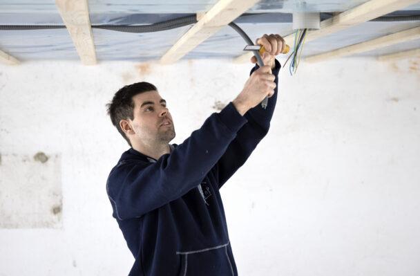 Jonas Isacsson arbetar med sladdar i ett tak