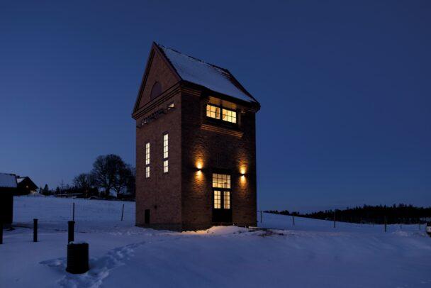 Transformatortornet, en hög tegelbyggnad, om natten. Det lyser varmt ur fönstren.