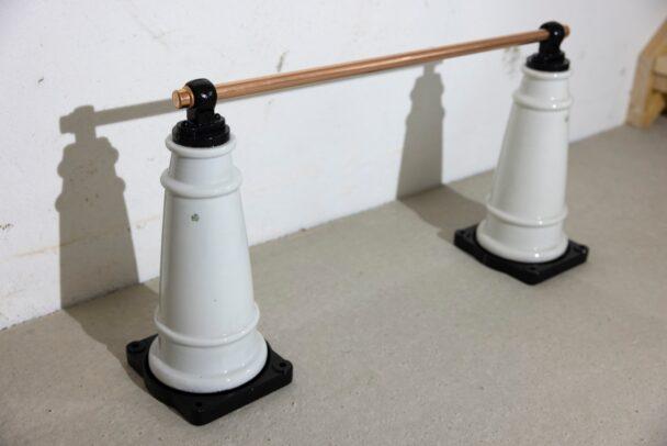 Två isolatorer med ett kopparrör mellan sig