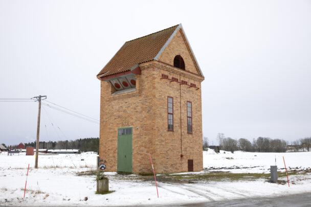 Tonet i Veckelstad: En hög tegelyggnad med sluttande tak och grön ytterdörr