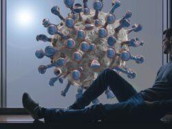 En man sitter i ett fönster och tittar ut på en stiliserad 3D-version av covid-viruset.
