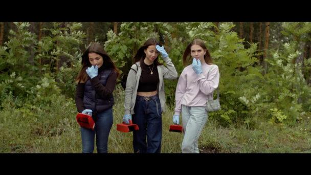 Tre unga personer med bärplockarutrustning i en skog