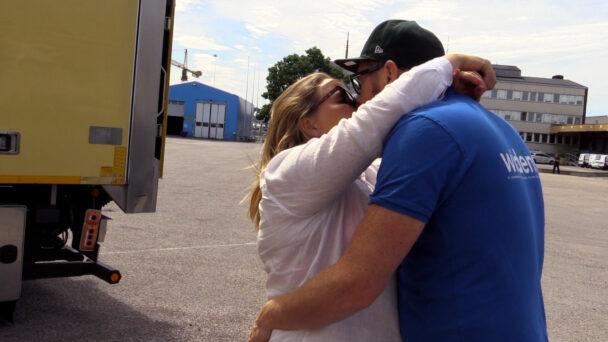 Två personer kysser varandra framför en lastbil