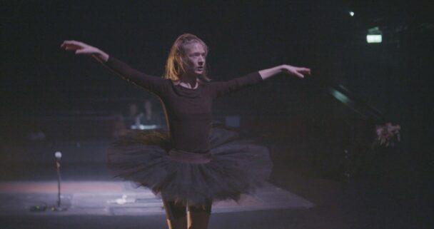 En person i ballett-kläder dansar på en scen
