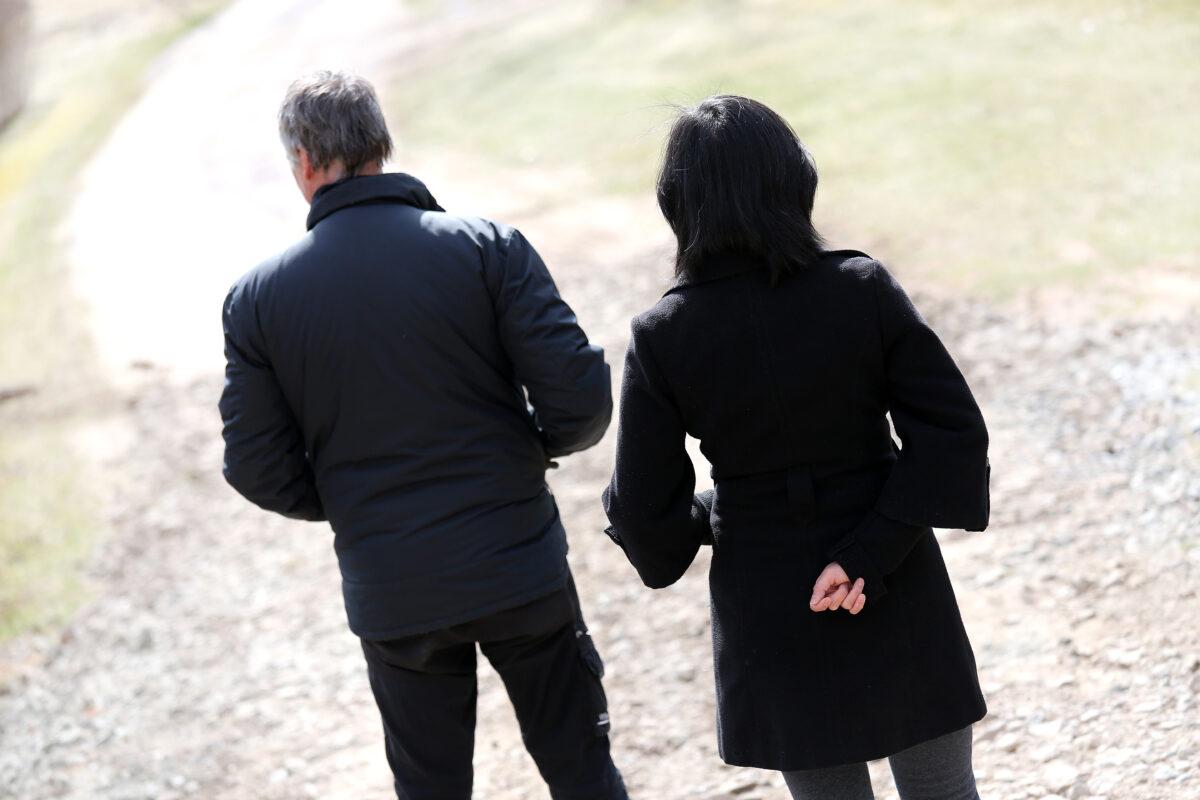 Ryggarna på två personer som står på en väg