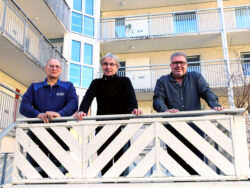 Roger Persson, Arne Forsberg och Mikael Gustafsson tittar ned över räcket på en veranda