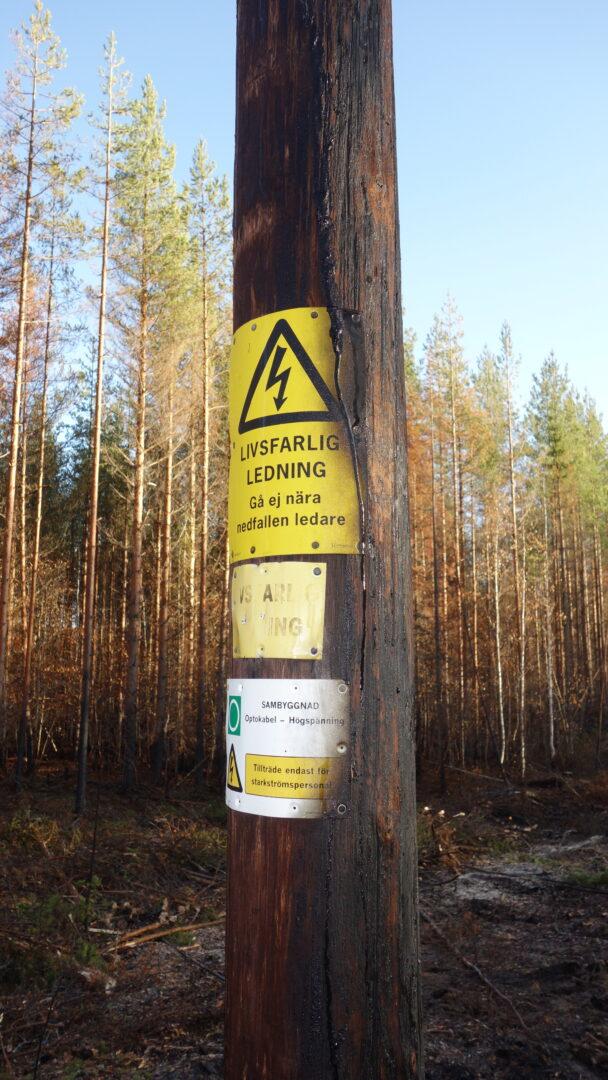 En elstolpe med varningsskylt på