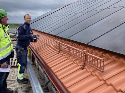 Personer i arbetskläder vid ett solcellstak