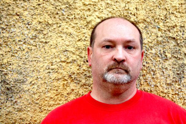 Johnny Ekdahl framför en gul husfasad.