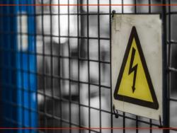 En varningsskylt för erfara på ett gallerstängsel