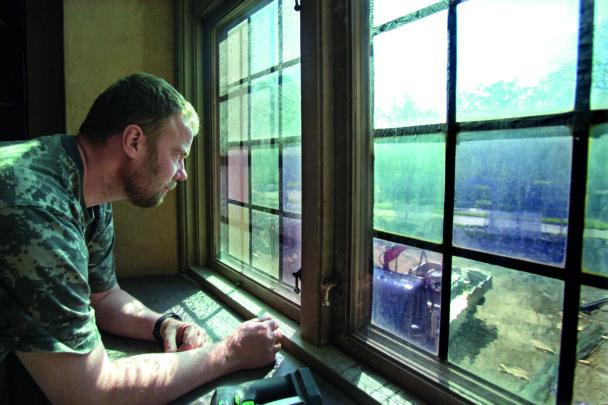 Klas Kristensson tittar ut genom ett kyrkfönster