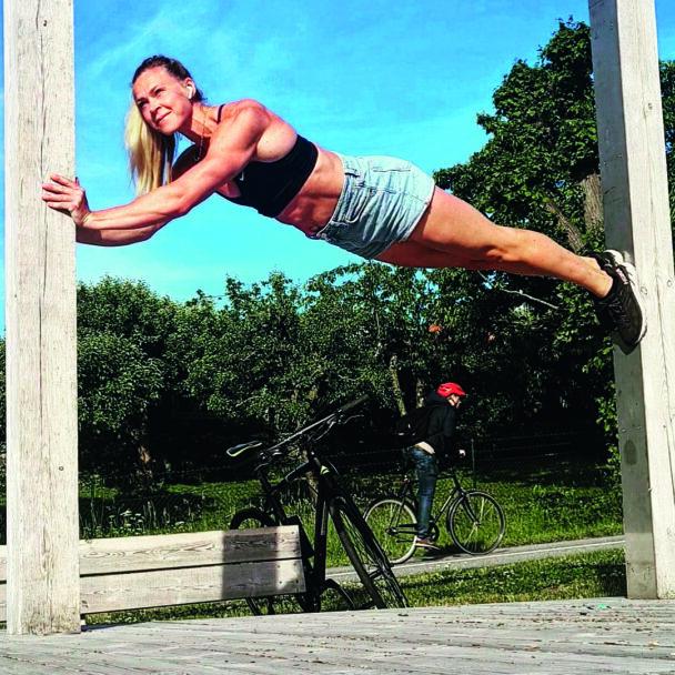 Sofia Österberg håller sig uppe med händer och fötter mellan två reglar