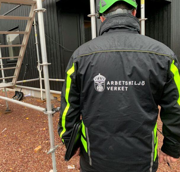 En person i Arbetsmiljöverkets jacka och hjälm på en byggarbetsplats